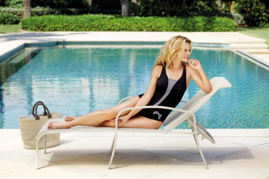Woman on lounge next to pool.